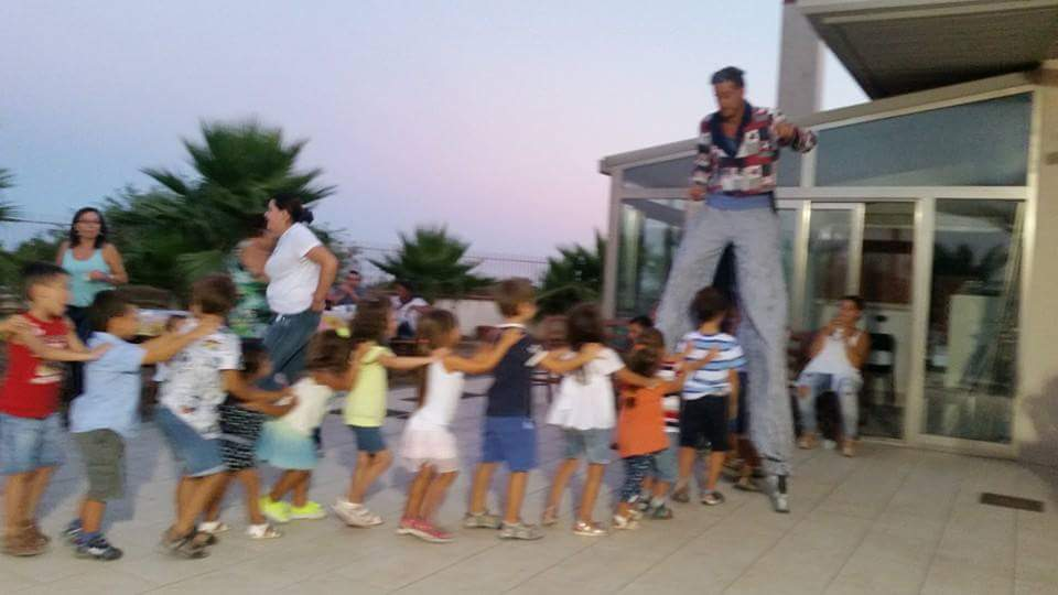 giocoliere sui trampoli di fronte ai bambini