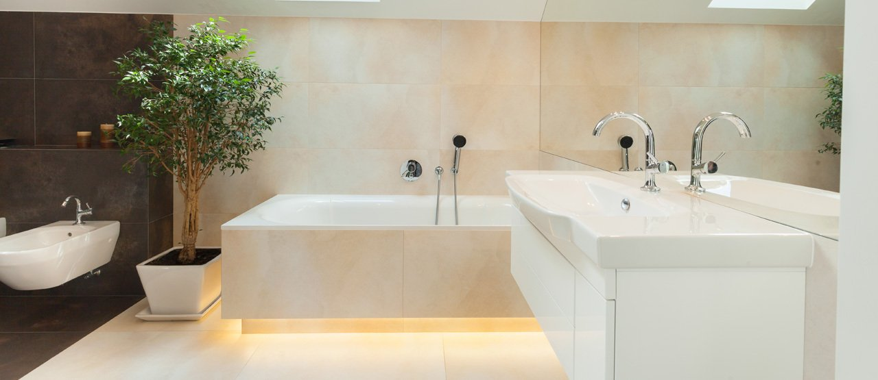 Bathroom with white suite and beige and cream wall and floor tiles