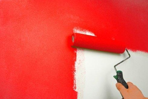 mano di una persona che imbianca un muro di rosso