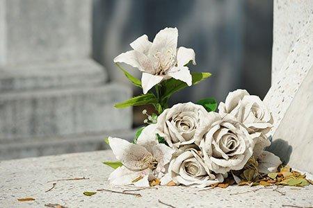Rose e gigli bianchi sulla tomba