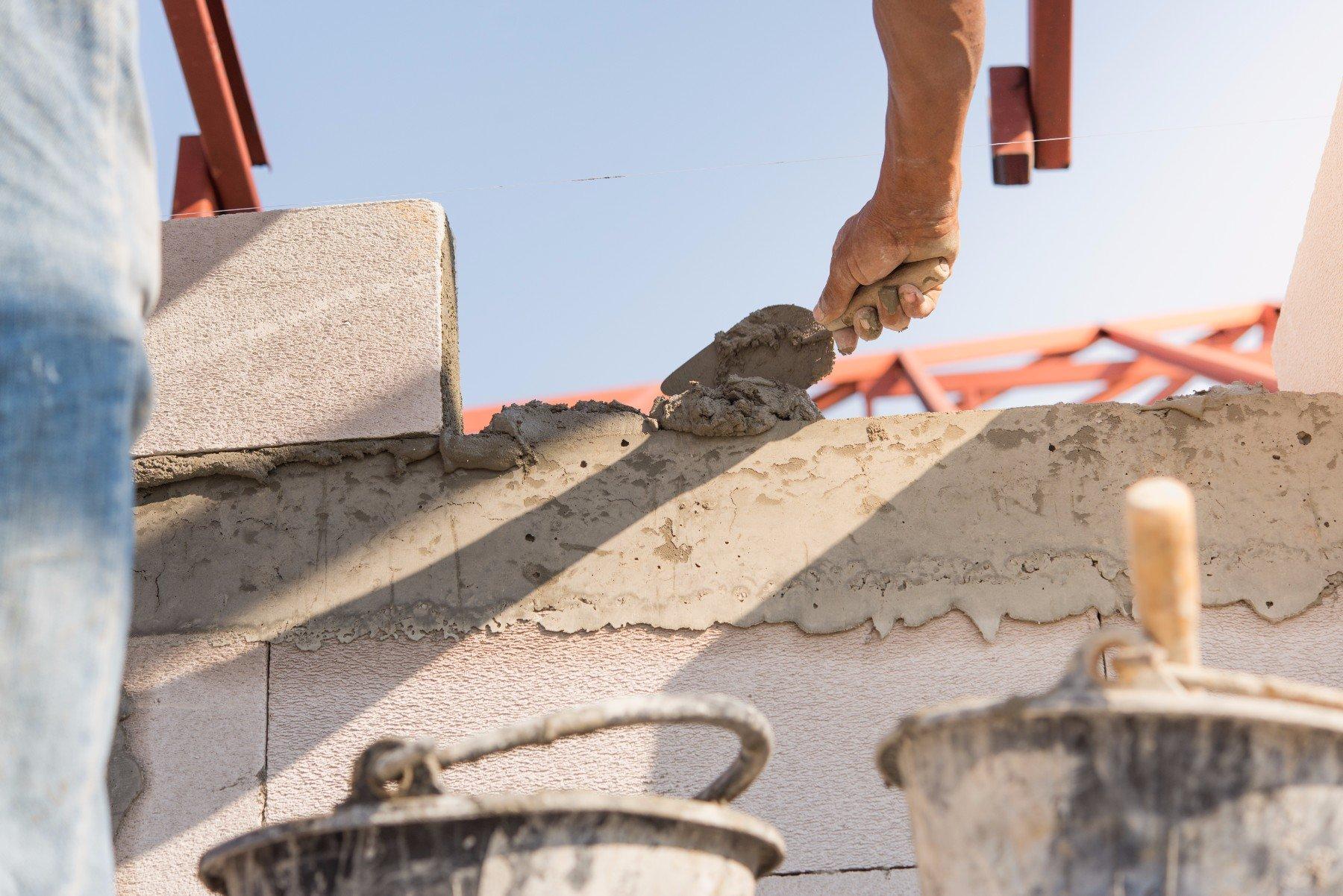 Muratore installando mattoni sul cantiere