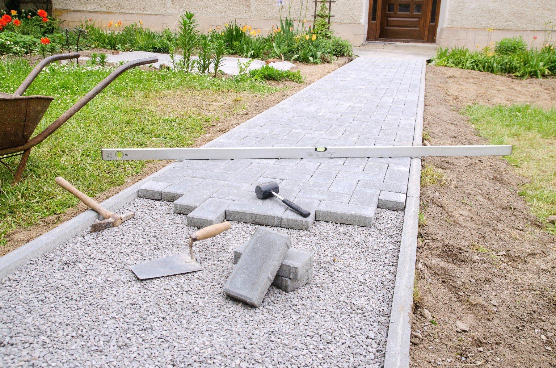 Il muratore mette i blocchi di pietra in calcestruzzo per costruire un patio