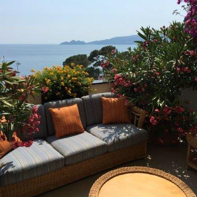 un divano azzurro con cuscini arancioni su un terrazzo con dei fiori