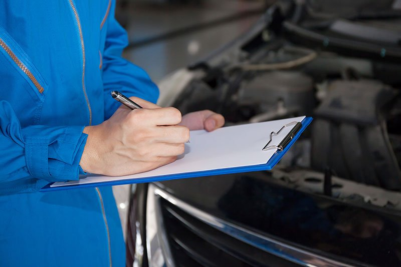 Young mechanic engineer taking a note on clipboard for examining a vehicle