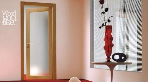 una porta in vetro e legno e un tavolino con un vaso di fiori
