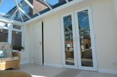 una porta da esterno di color bianco e due finestre in PVC