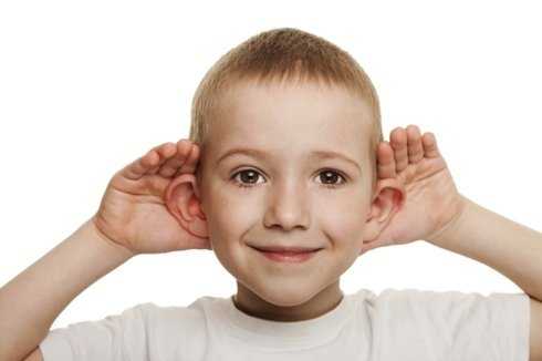 un bambino che mima il gesto di ascoltare
