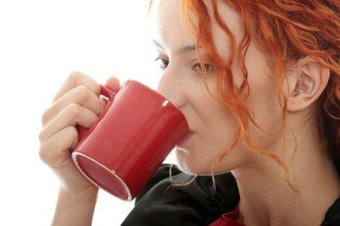 una donna con capelli arancioni che beve con una tazza