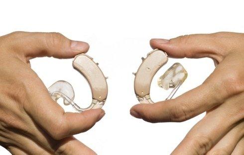 due mani che tengono due apparecchi acustici
