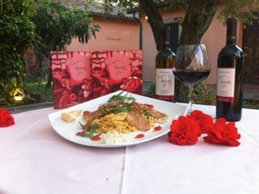 Piatto di cibo, fiori e  coppa di vino