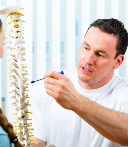 un uomo che con una penna indica una spina dorsale