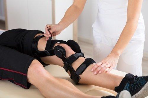 due mani che mettono un tutore al ginocchio di un uomo sdraiato