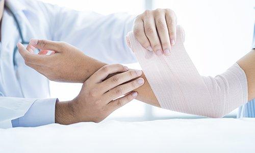 delle mani di un medico che applicano una fasciatura a un braccio di un ragazzo