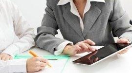uomo e donna seduti ad una scrivania, donna con tablet in mano, uomo che prende appunti