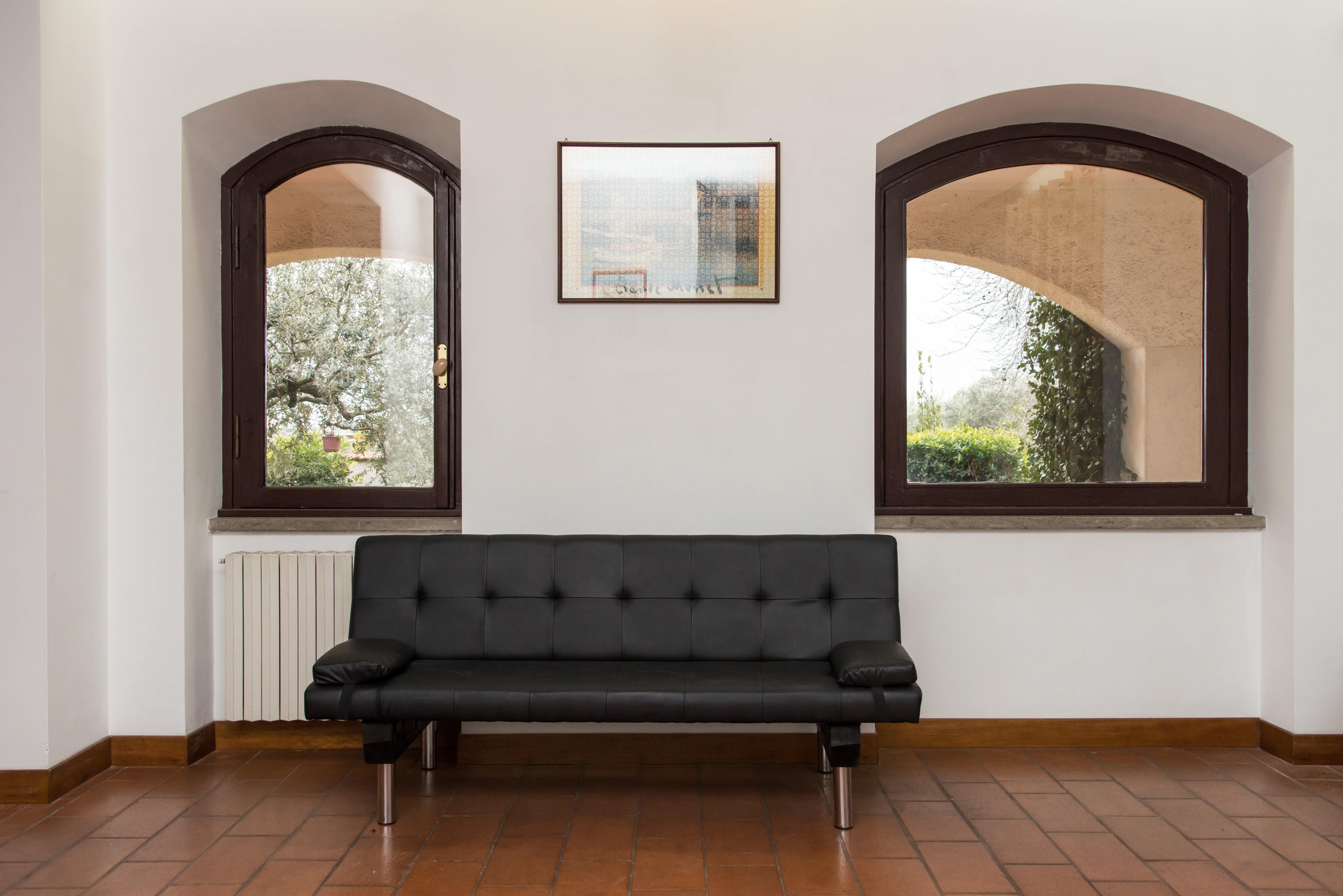 divano nero sotto due finestre