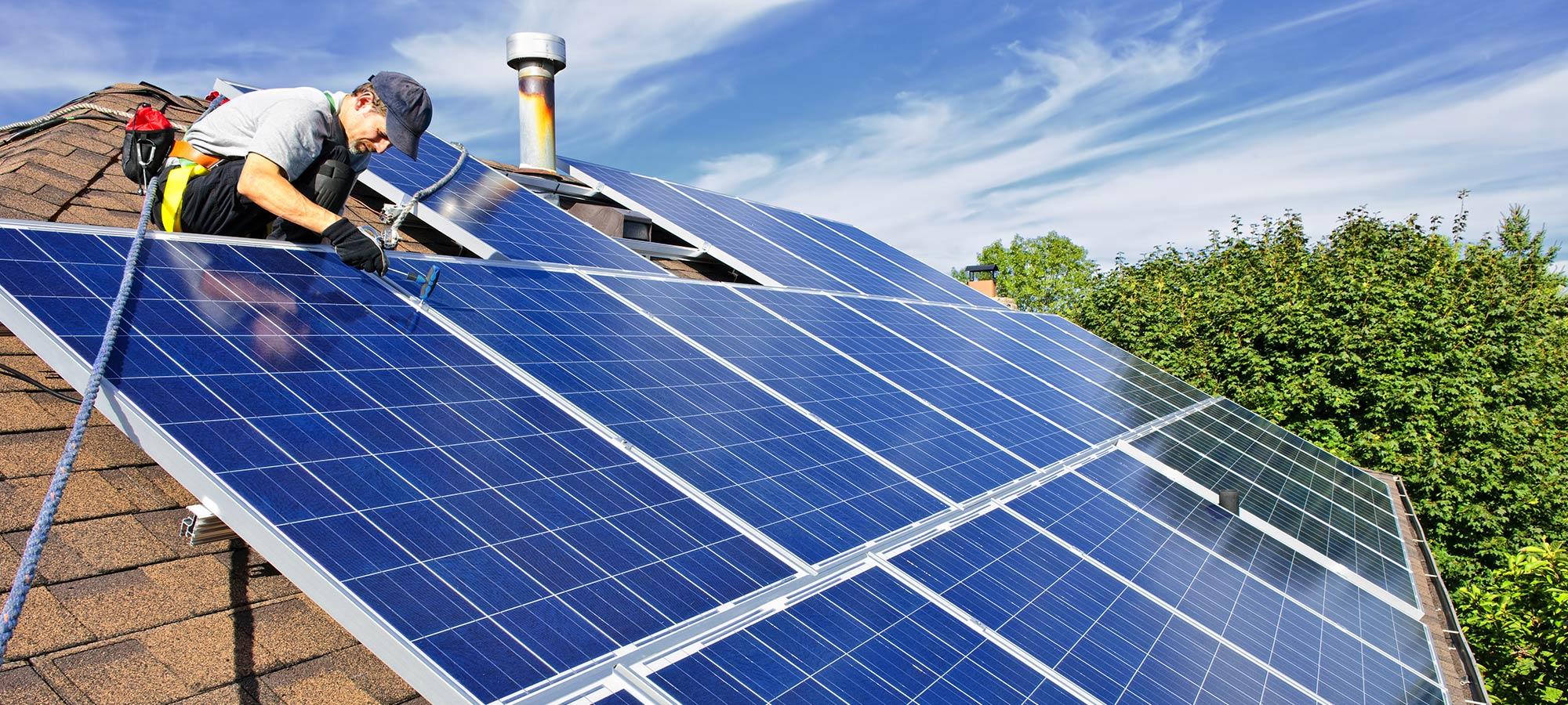 Addetto mentre installa pannelli solari sul tetto