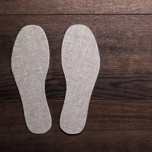 A pair of insole orthotics on a wood floor
