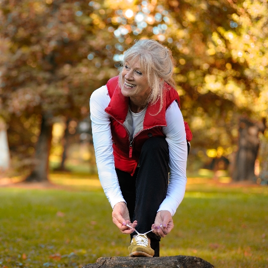 An older woman ties her shoes in a park