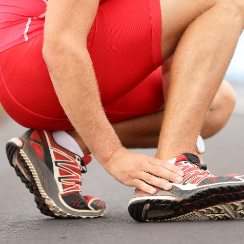An athlete holds their heel in pain