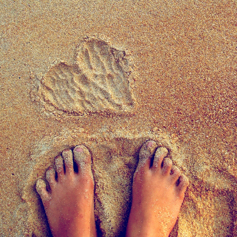 Woman's feet in the sand with a heart drawn in the sand