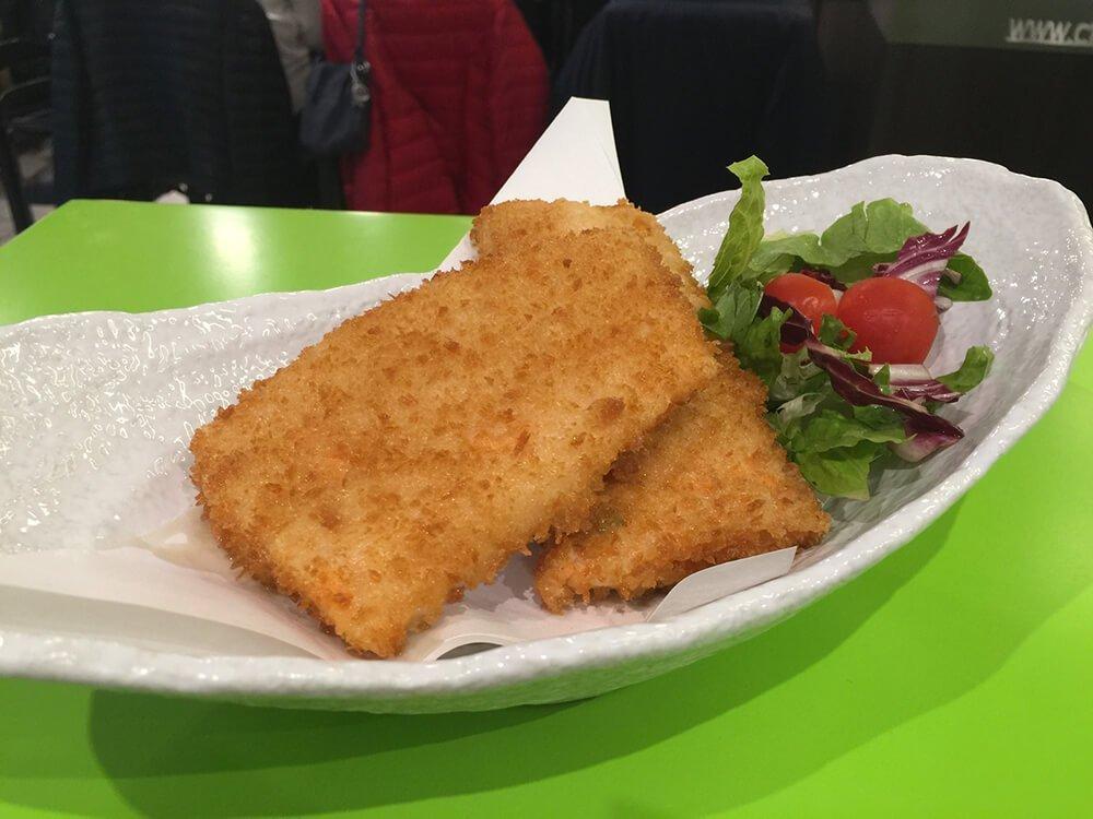 Pesce fritto in piatto bianco.