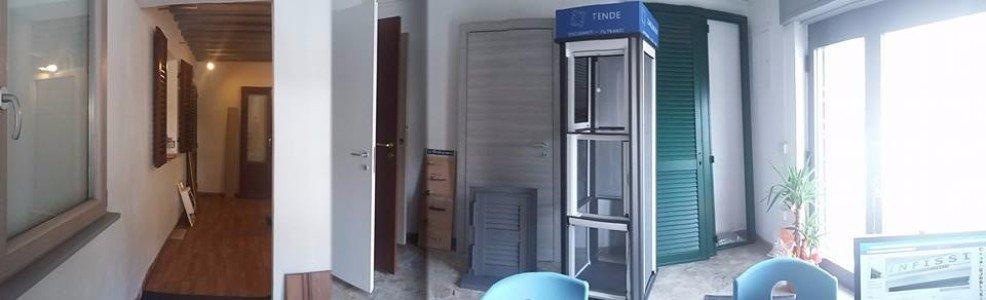 un corridoio e sulla destra porte, finestre e persiane di diversi colori