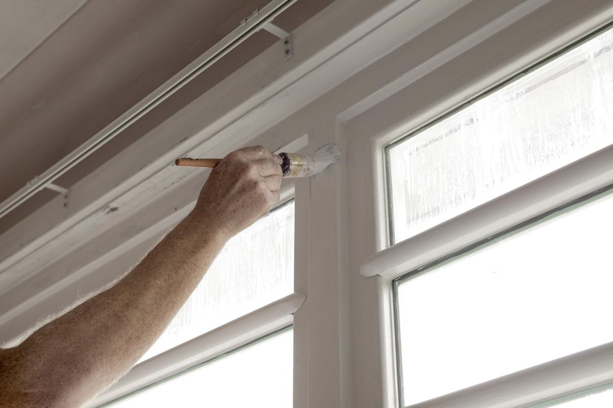 Home contractor painting windows in Bullhead City, AZ
