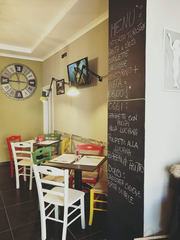 tavolini di una trattoria con menu scritto alla lavagna