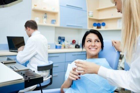 una ragazza seduta dal dentista e accanto una donna che le da un bicchiere d'acqua