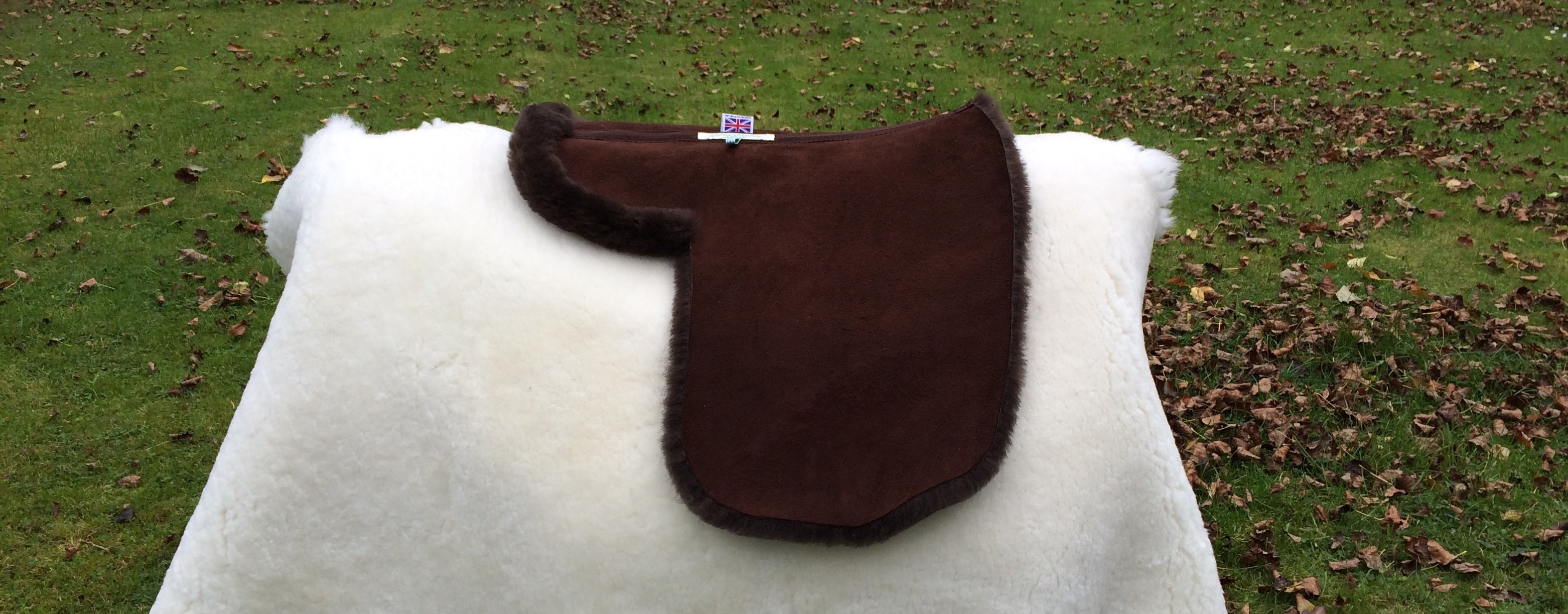 Showing Numnah with Turned Edges around Seat and Back of Flaps. Dark Brown, Black ( not on a grey horse), Ivory, Cream