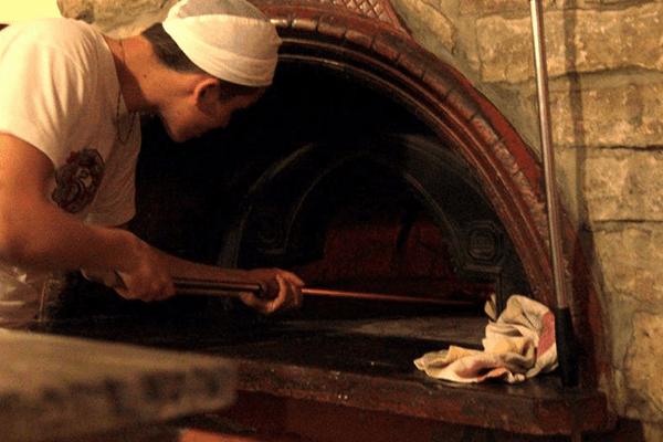 pizzaiolo che inforna una pizza