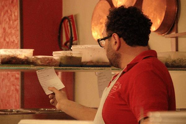 un pizzaiolo prende guarda l'ordinazione