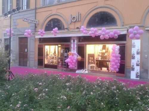 vetrina di negozio decorato con palloncini rosa