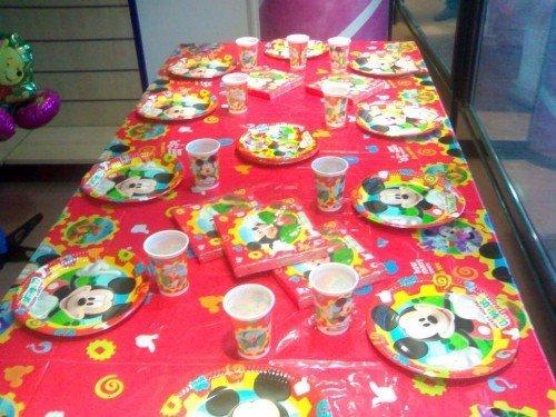 tavolo con tovaglia, bicchieri e piatti colorati