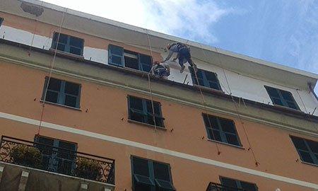 un uomo con un imbracatura appeso a delle corde sulla facciata di una casa