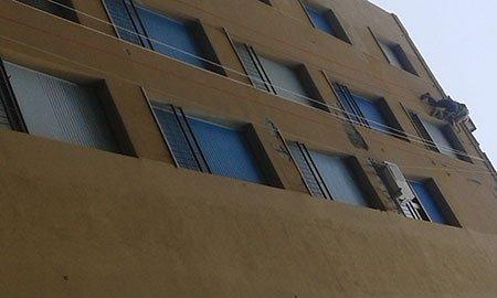 un uomo su una facciata di una casa appeso a delle corde