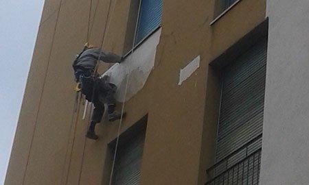 un uomo appeso a una corda al lavoro su una facciata di una casa
