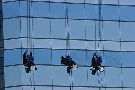 tre persone con delle imbracature al lavoro sulla facciata di un palazzo