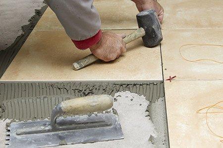 una mano con un martello appoggiato su una piastrella