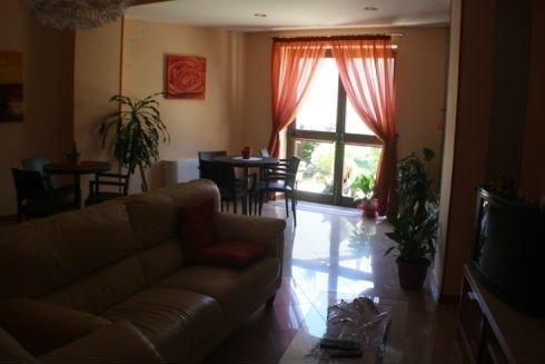 sala comune della casa di riposo con tavolini, sedie e divano