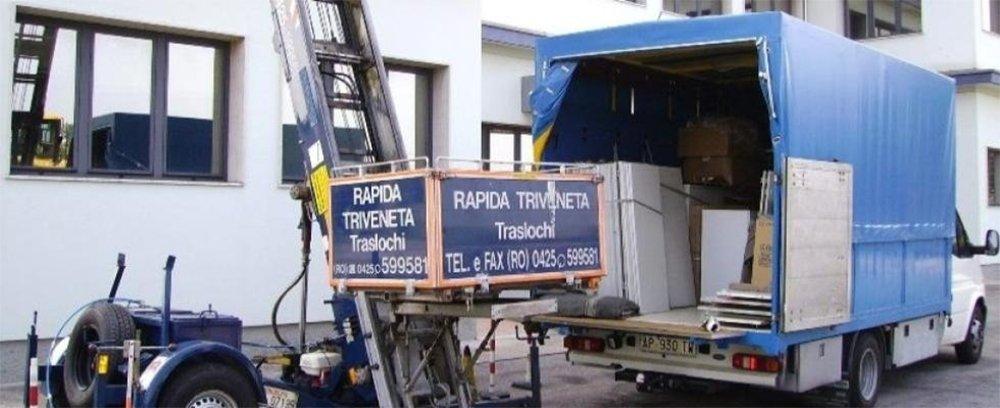 una scala aerea con una piattaforma e un camion dei traslochi