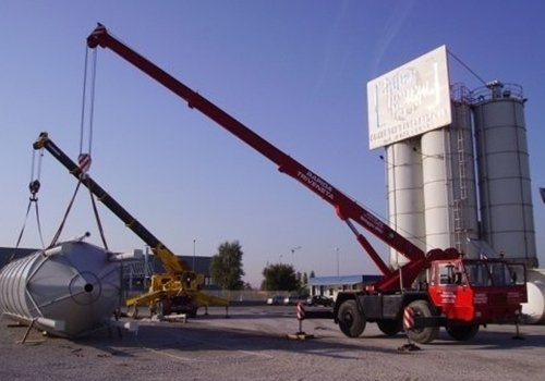 due auto gru che sollevano un silos