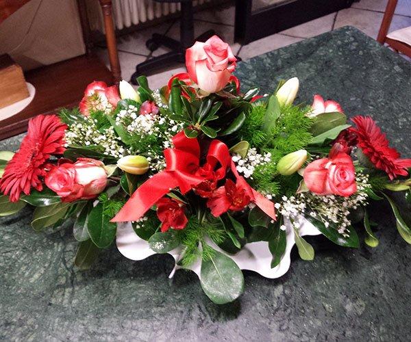 una composizione di rose rosse con un fiocco e fiori non ancora sbocciati