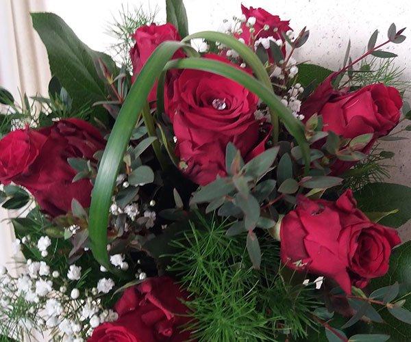 un bouquet di rose rosse e dei fiorellini bianchi