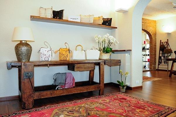un tavolo e una mensola in legno con delle borse di color bianco, beige e nero