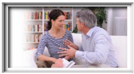 coppia che discute animatamente, divano bianco, libreria di sfondo