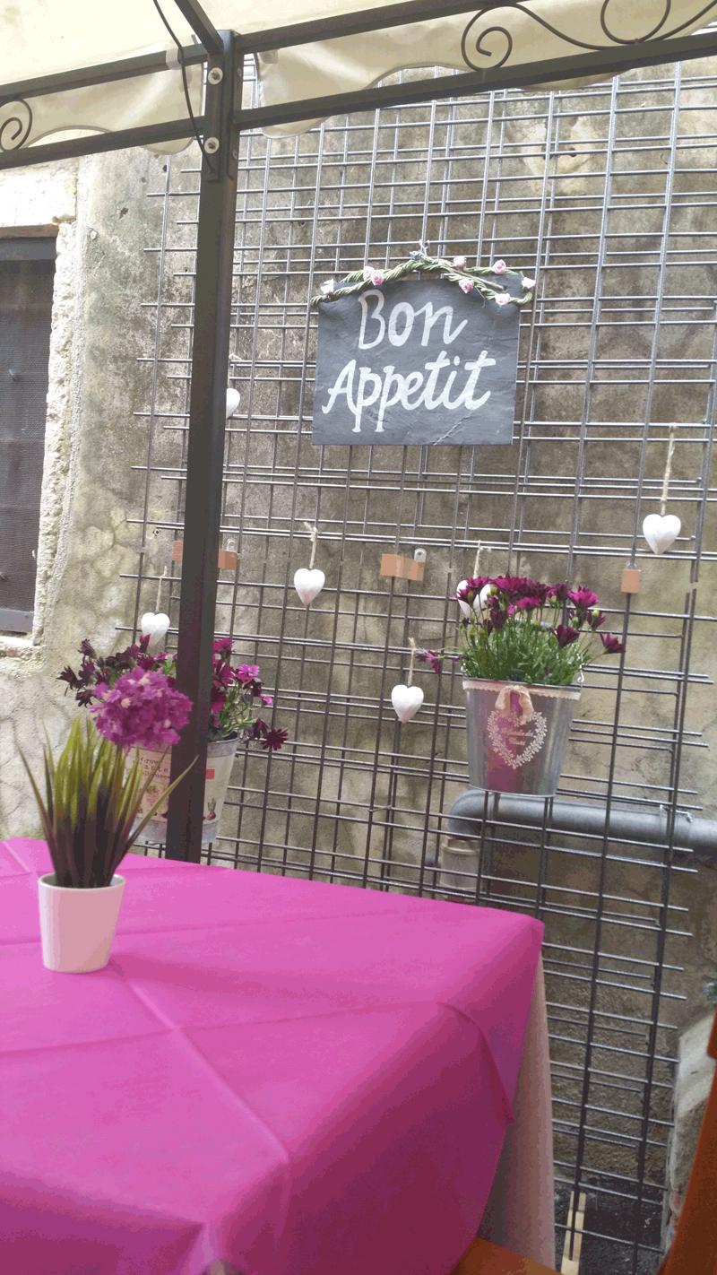 vaso di fiori sul tavolo e anche scritto un cartello BON  APETIT