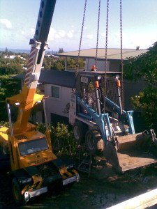 yellow crane truck lifting mini bobcat