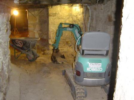 mini excavator in tunnel with yellow lights