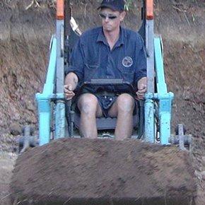 man operating mini excavator